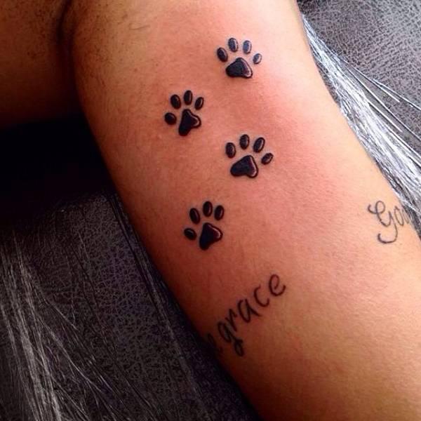 Tatuaje De Cuatro Huellas De Perros En El Bicep De