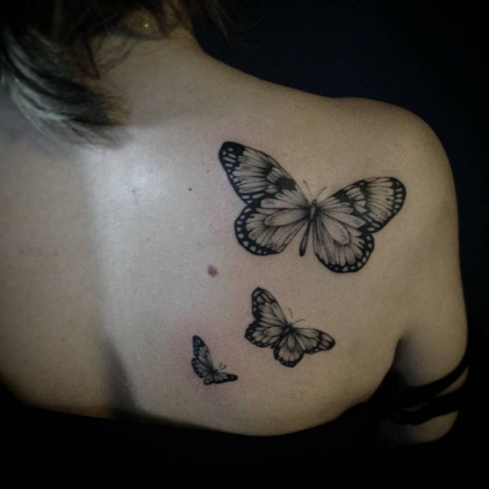 Shoulder blade tattoo of three butterflies by Ivy