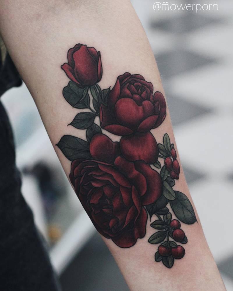 Illustrative red rose tattoo on the left inner forearm.