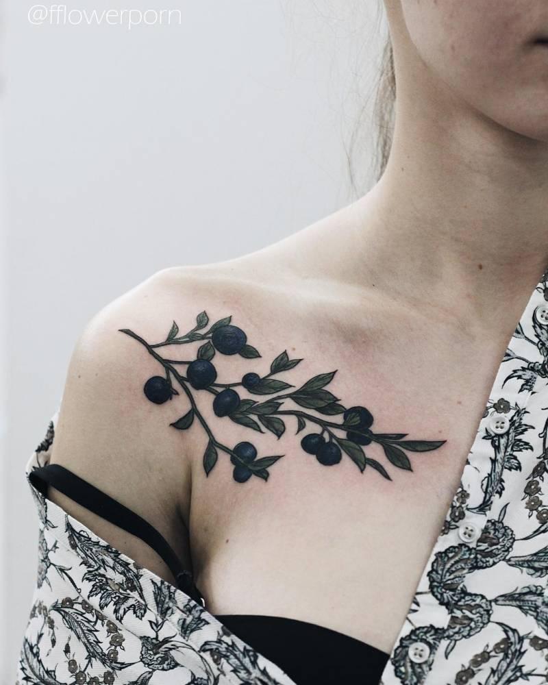 Illustrative blueberry chest tattoo.