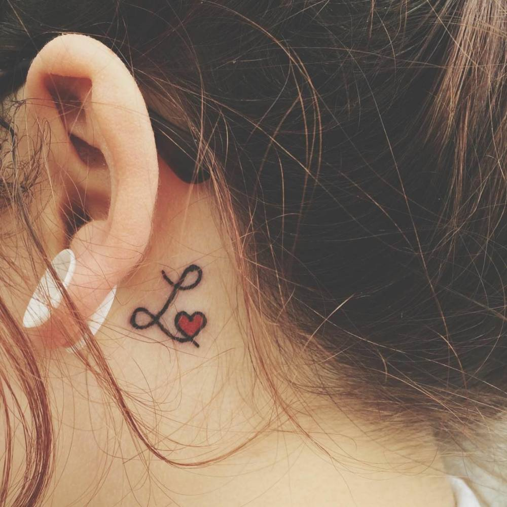 Behind The Ear Tattoo Of Letter L Together With A Red