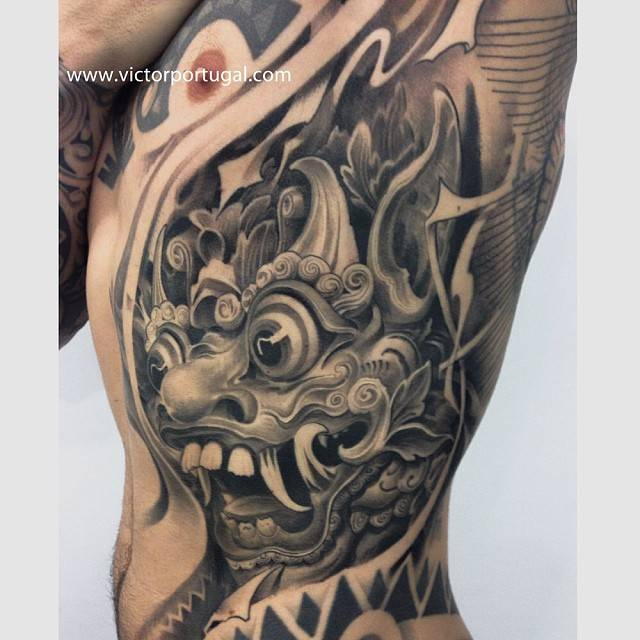 Black and grey style Barong tattoo on the left side.