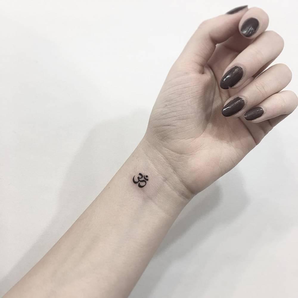 Om tattoo on the inner wrist.