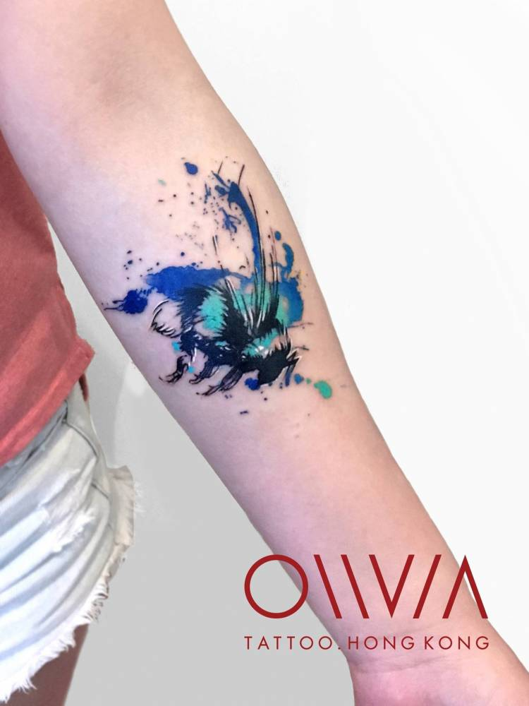 Watercolor bee tattoo on the left inner forearm.