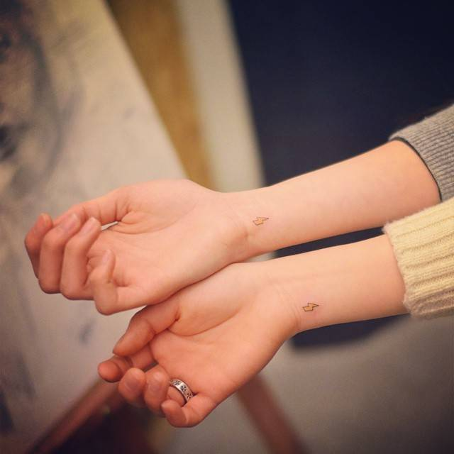 Tiny matching bolt tattoos on the wrist.