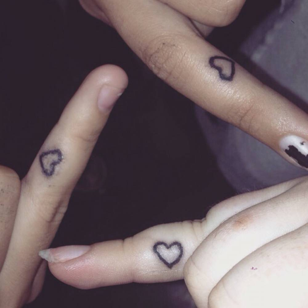 Three finger matching tattoos of a heart on Lexie and