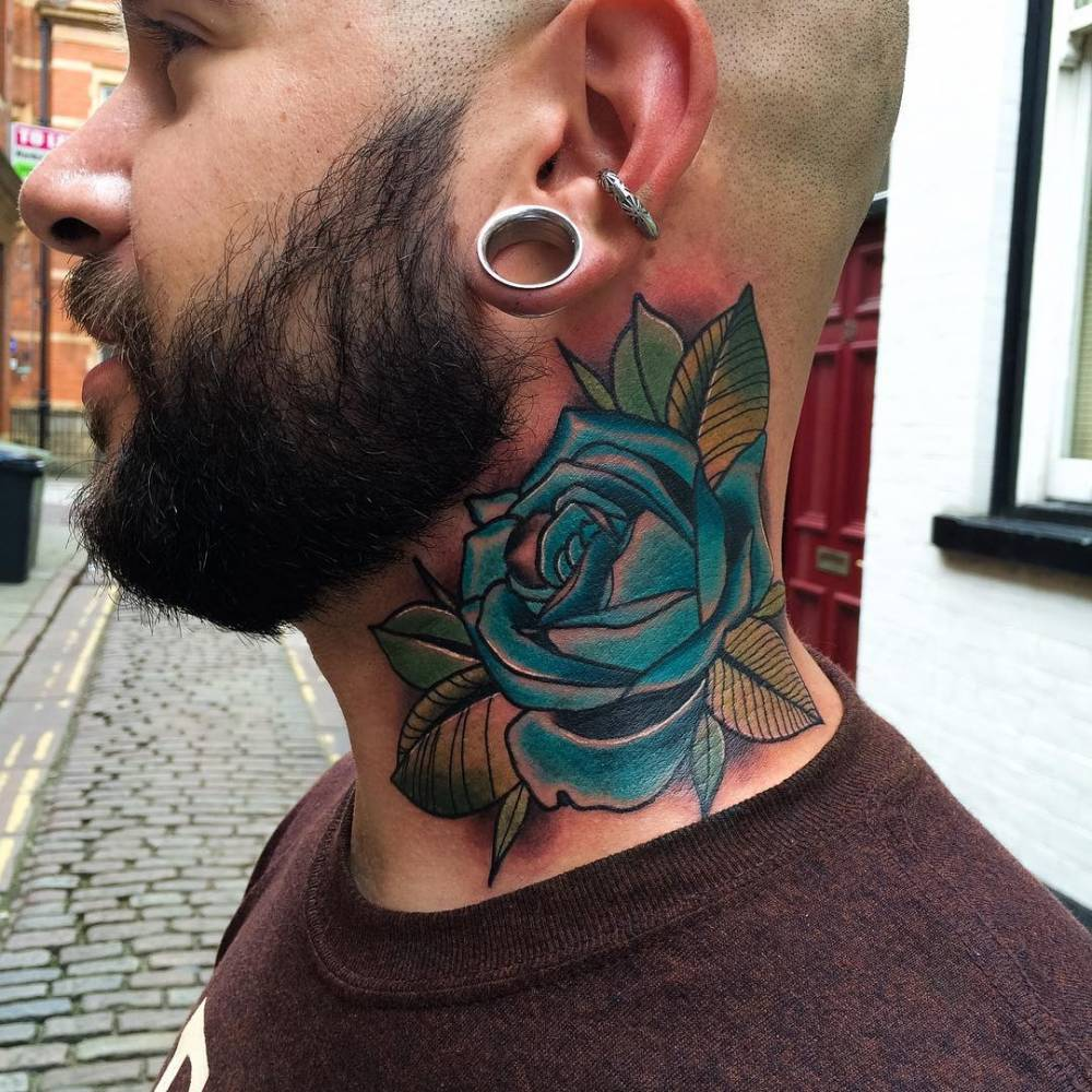Traditional blue rose tattoo on the left side of the neck.