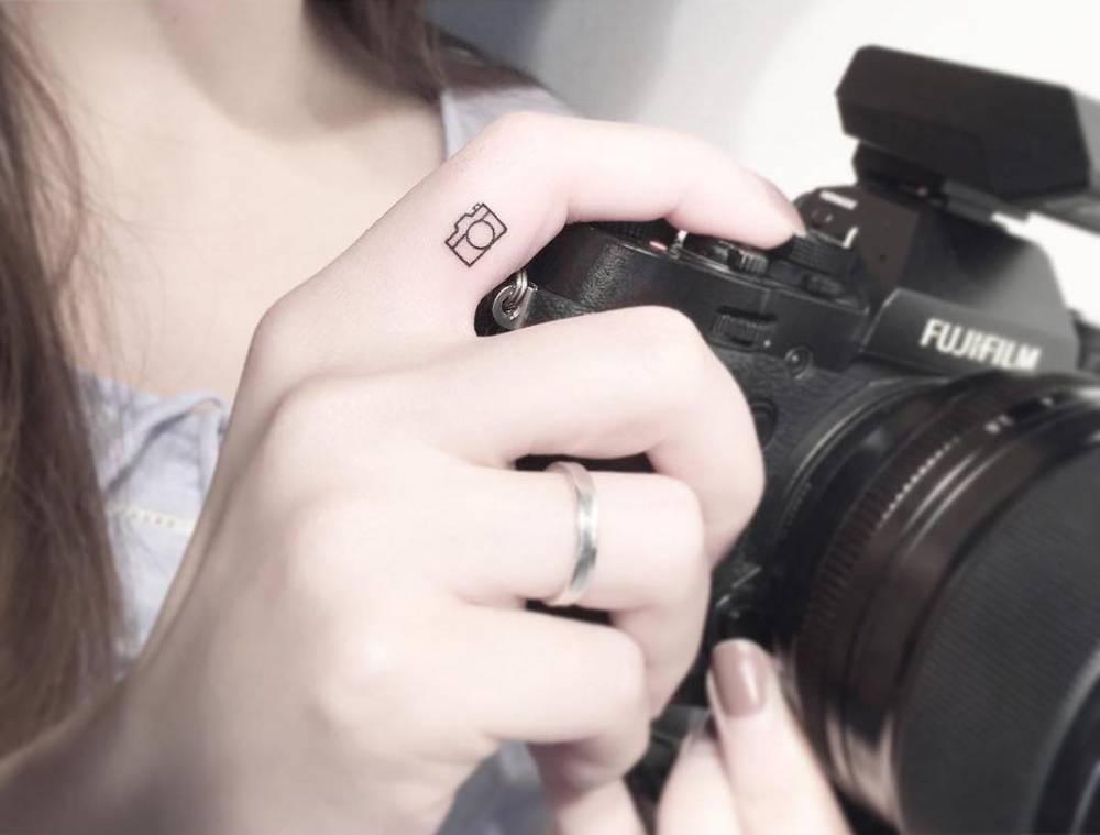 Reflex camera tattoo on the right index finger.