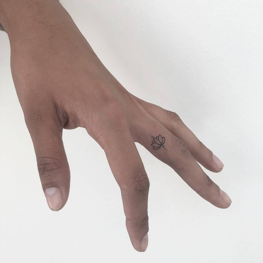 Minimalist fine line lotus tattoo on the finger.