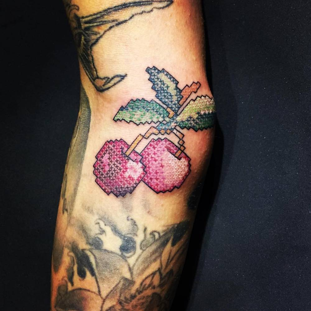 Cross stitch cherry tattoo on the right elbow.