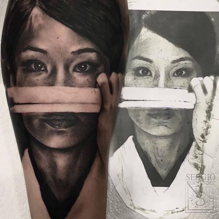 Kill Bill's O‑Ren Ishii (Lucy Liu) black and grey portrait tattoo on the inner forearm.