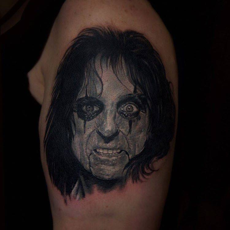 Realistic Alice Cooper portrait tattoo on the left upper arm.