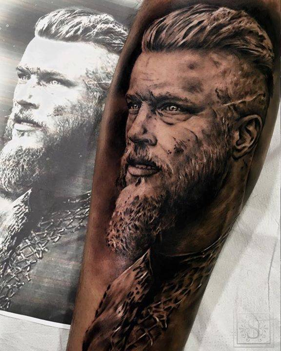 Black and grey style Ragnar Lodbrok tattoo on the right inner forearm.