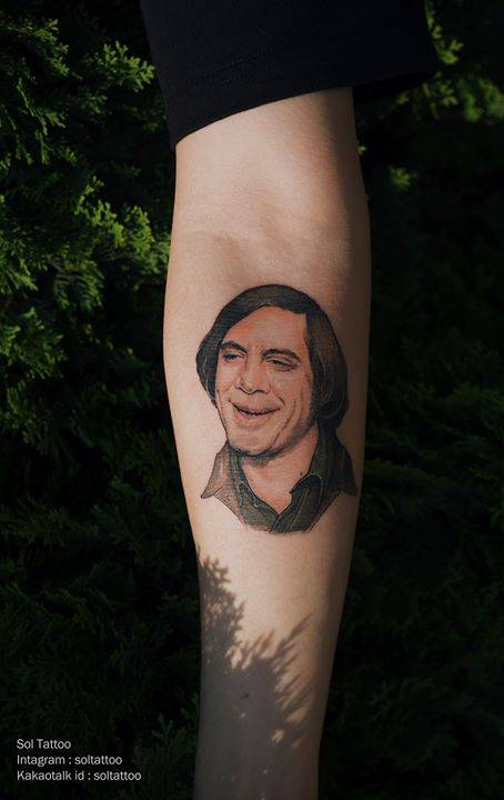 Realistic Anton Chigurth (Javier Bardem) from 'No Country for Old Men' portrait tattoo on the right inner forearm.