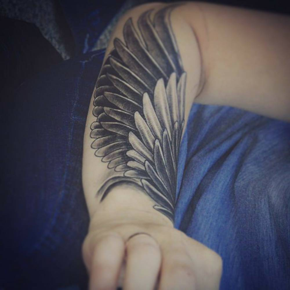 842803466 Forearm tattoo of a wing.
