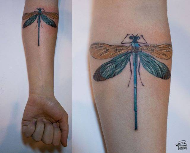 Dragonfly tattoo on the left inner forearm.