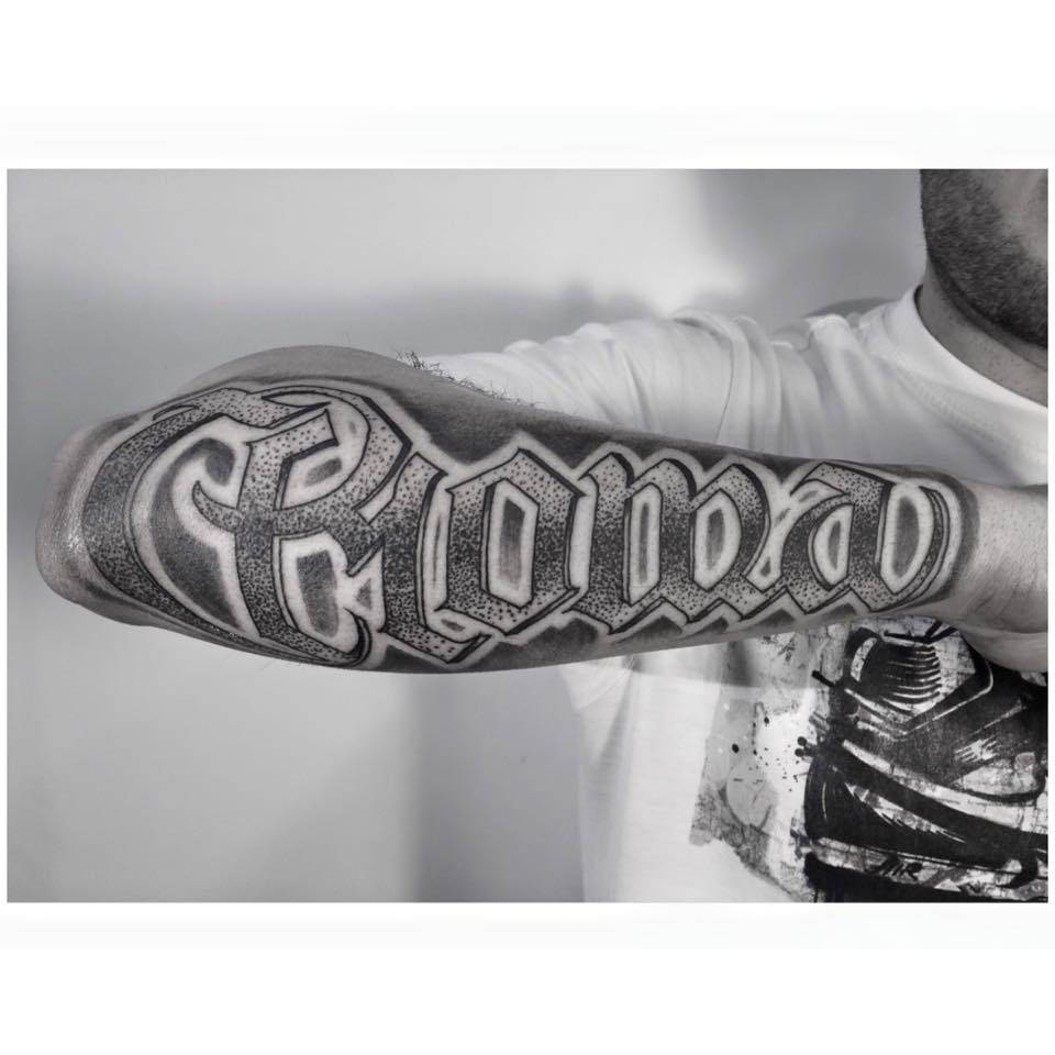 """Lettering """"Roma"""" tattoo on the forearm."""