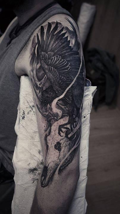 Deer skull and raven tattoo on the left upper arm.