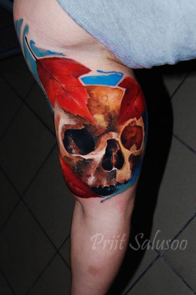 Realistic skull tattoo on the right inner arm.