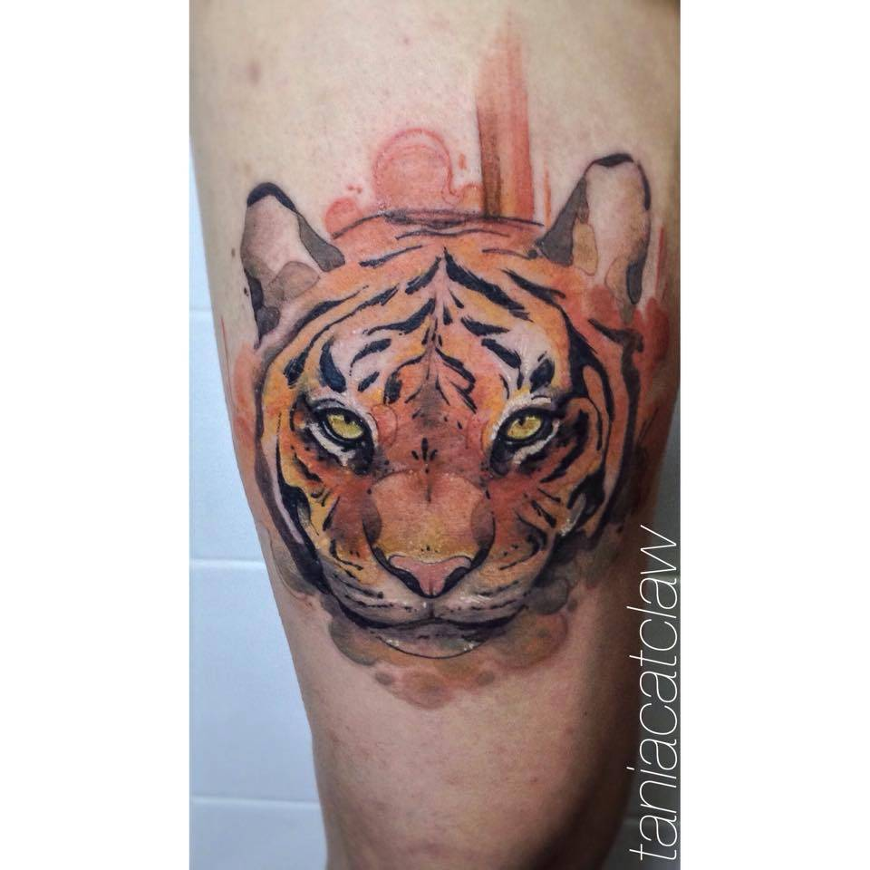 Sketch work tiger face tattoo on the right thigh.