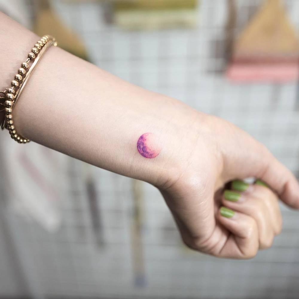 Purple moon tattoo on the left inner wrist.