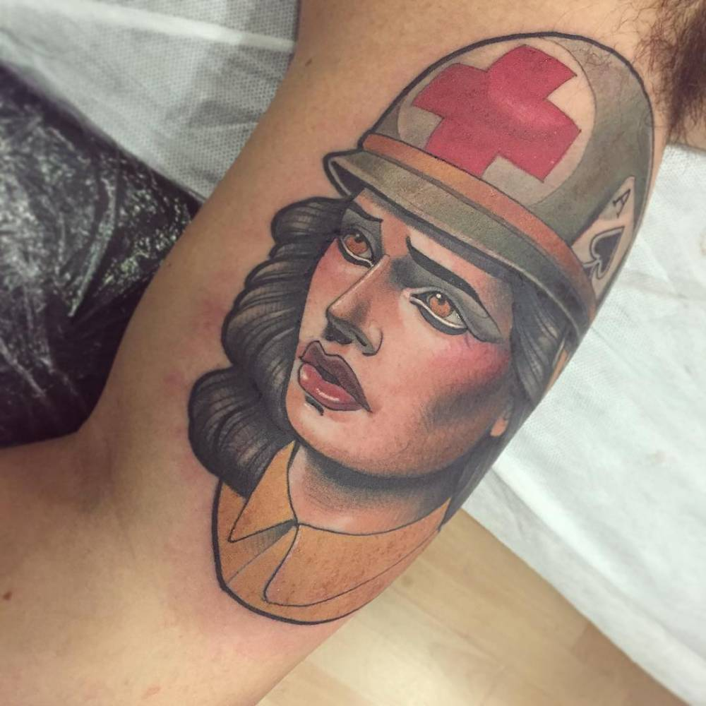 Neotraditional army nurse tattoo on the right inner arm.