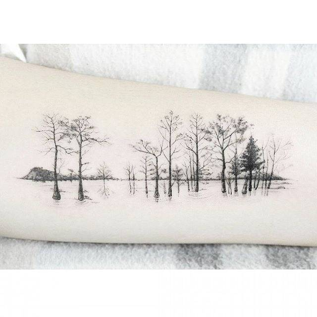 Water forest tattoo on the inner forearm.