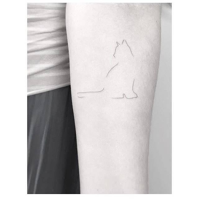 Minimalist cat tattoo on the inner forearm.