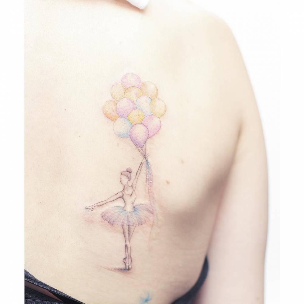 Ballet dancer holding balloons tattoo on the back.