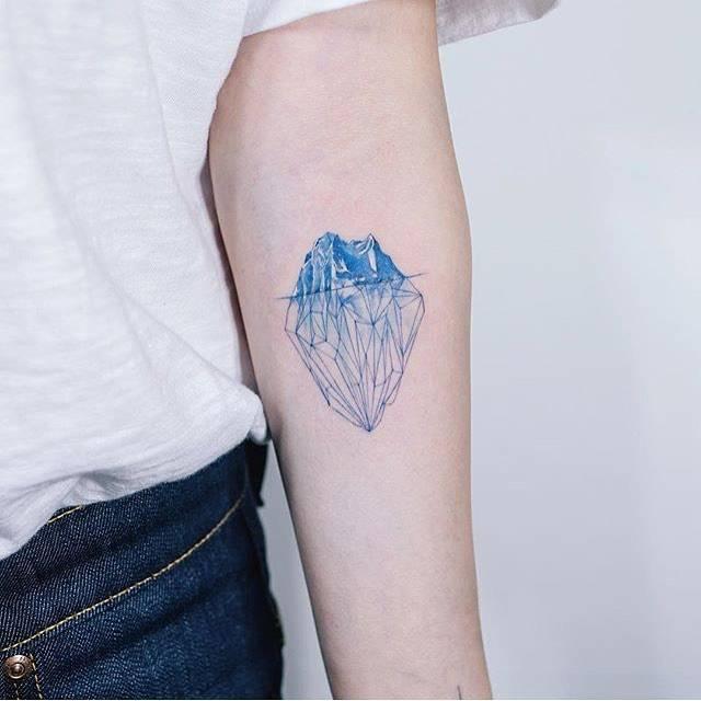 Iceberg tattoo on the left inner forearm.