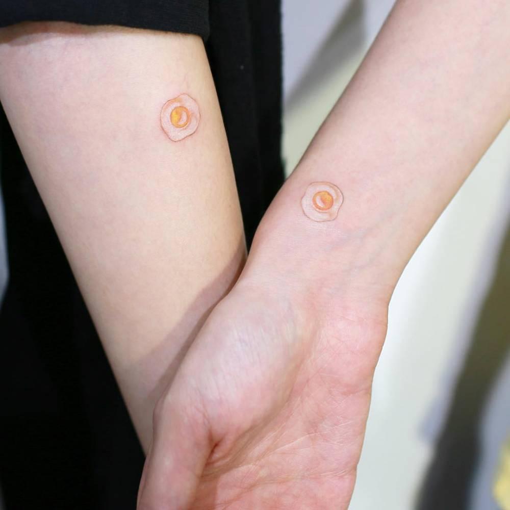 Matching fried egg tattoos.