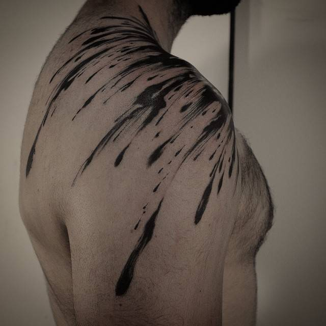 Abstract brush stroke tattoo on the right shoulder.