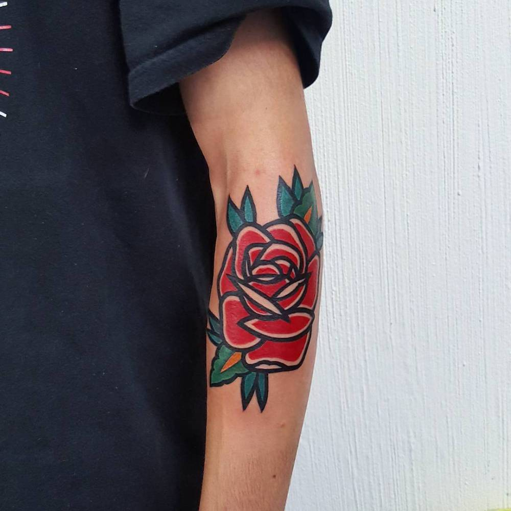 Bold traditional red rose tattoo on the left forearm.