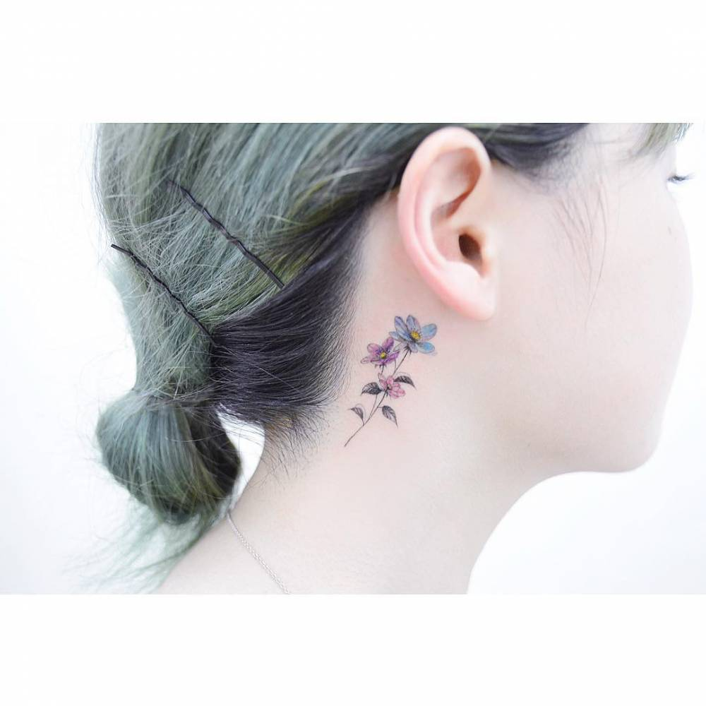 Anemone tattoo behind the right ear.