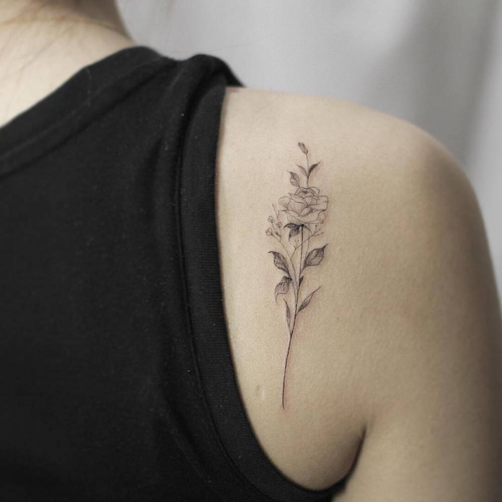 Fine line rose tattoo on the right shoulder blade.