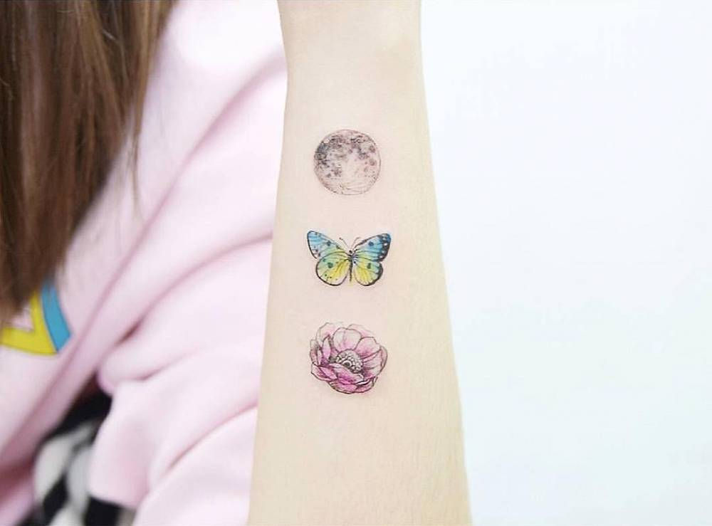 Moon, butterfly and flower tattoo on the forearm.