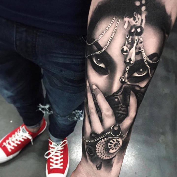 Black and grey Persian lady portrait tattoo on the left inner forearm.