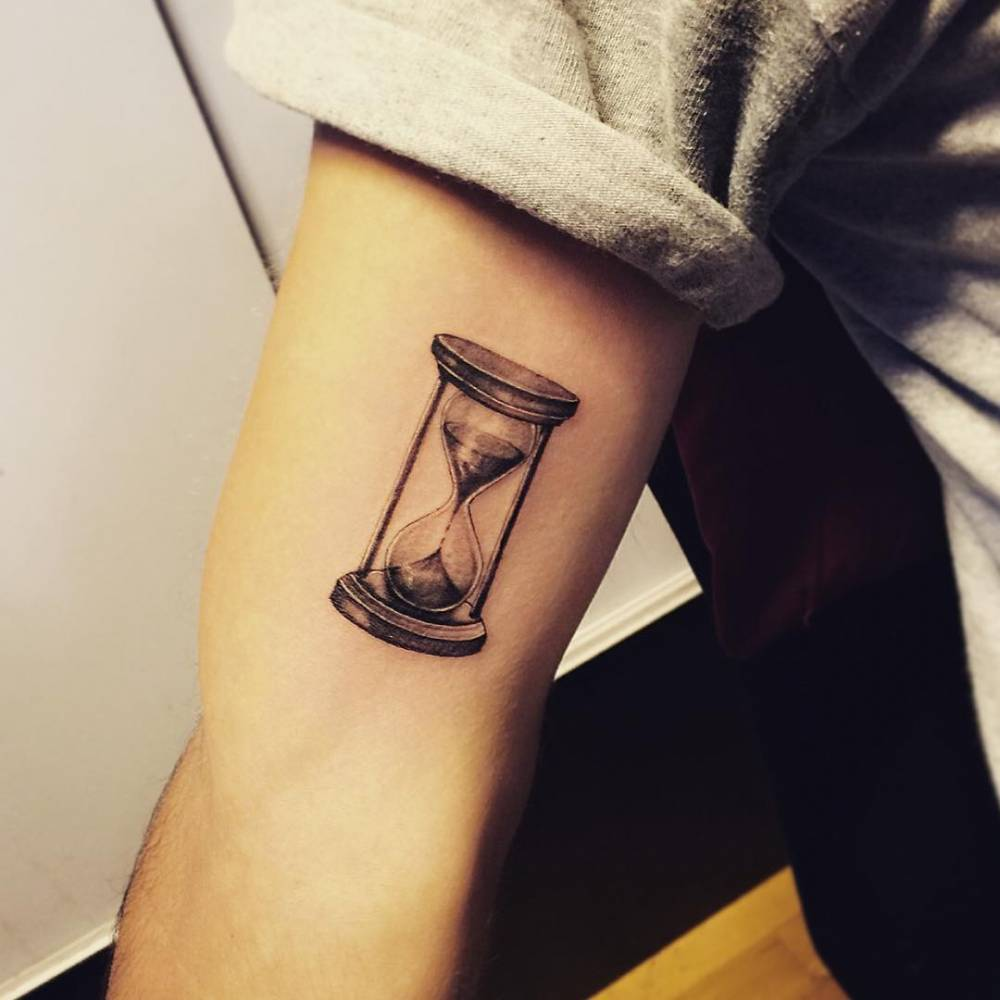 Fine line hourglass tattoo on the right inner arm.