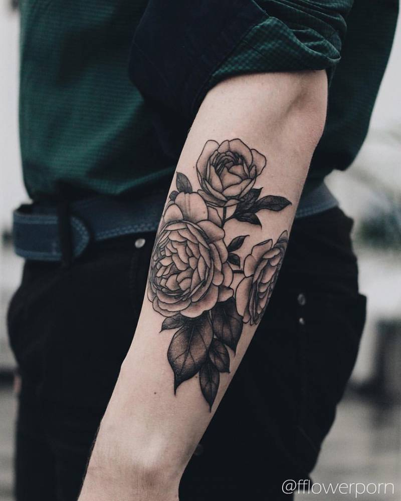 Black and grey peonies on the left forearm.