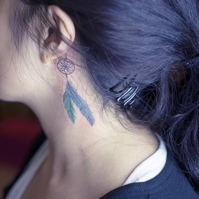 Dreamcatcher tattoo behind the left ear.