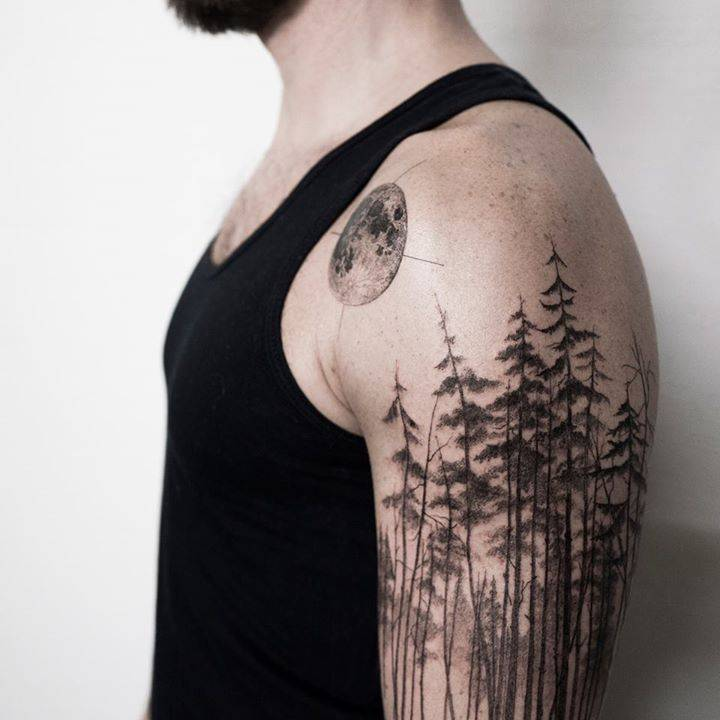 Pine tree forest tattoo on the left upper arm.