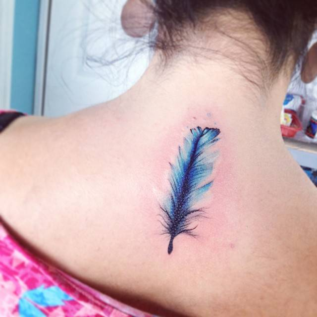 2fa27ecc563a3 Blue watercolor style feather tattoo on the upper back.
