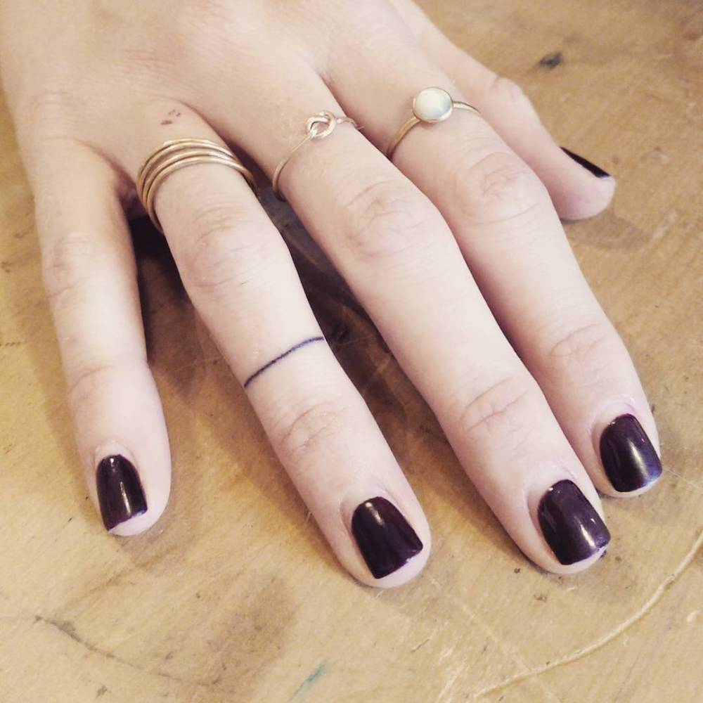 Minimalist ring tattoo on the right ring finger.