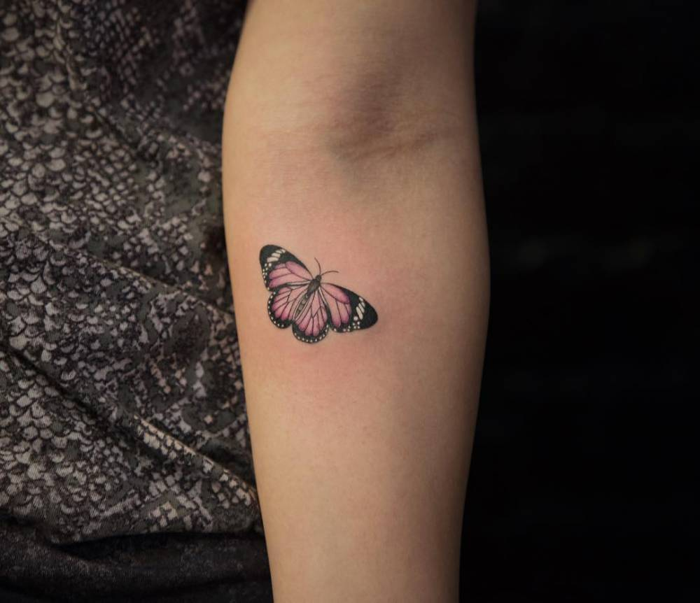 Butterfly tattoo on the inner forearm.