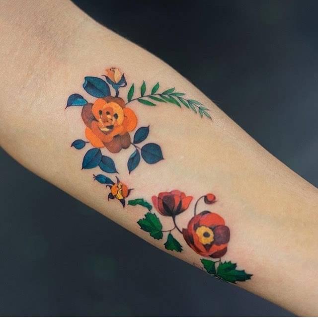 Orange rose and poppy tattoos on the left inner forearm.