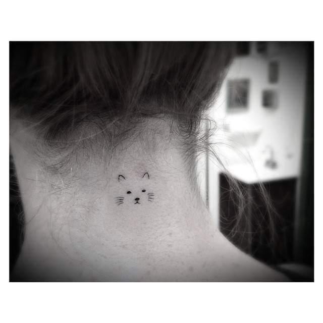 Minimalist cat face tattoo on the back of the neck.