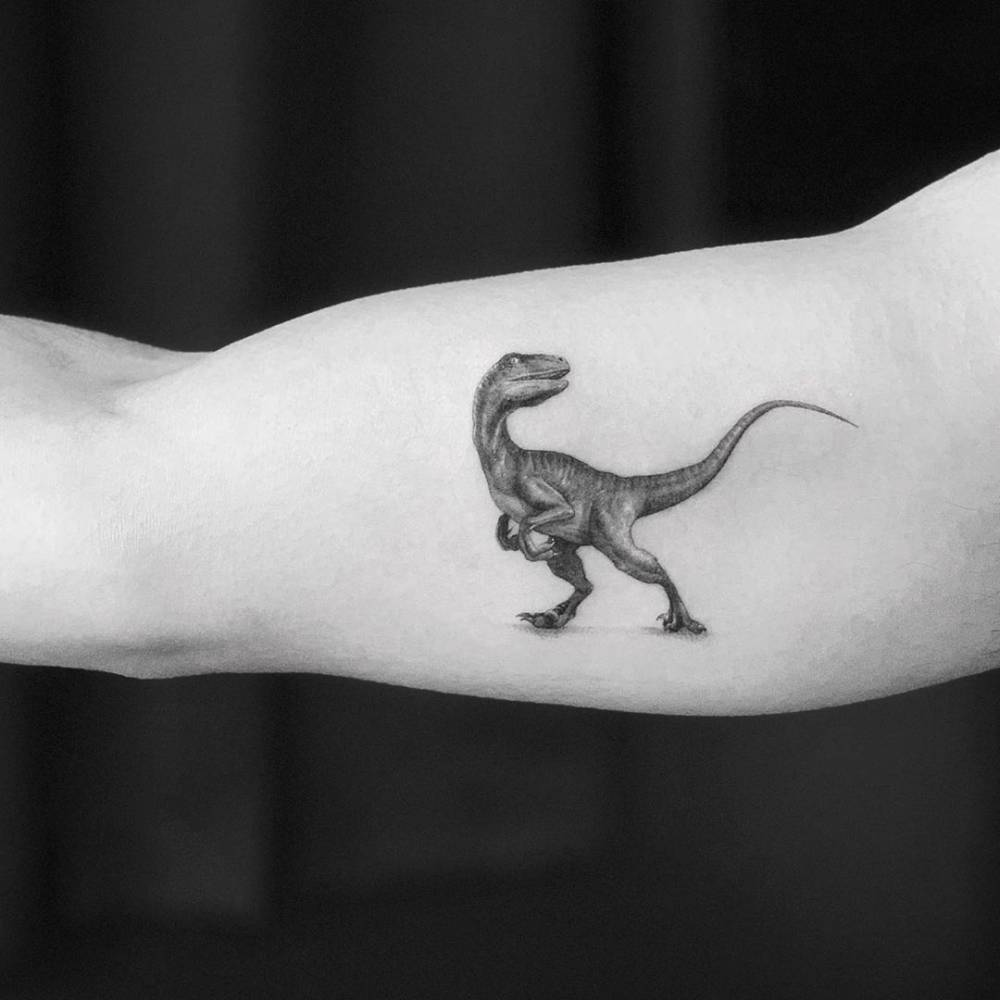 SIngle needle T-Rex tattoo on the right inner arm.