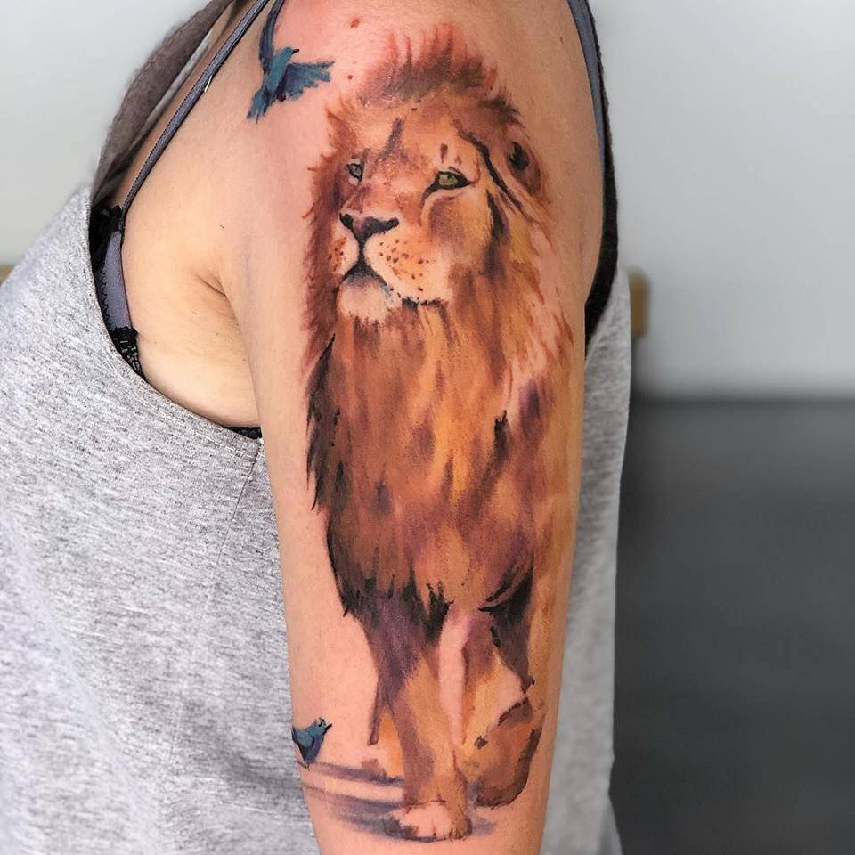 Watercolor lion tattoo on the upper arm.