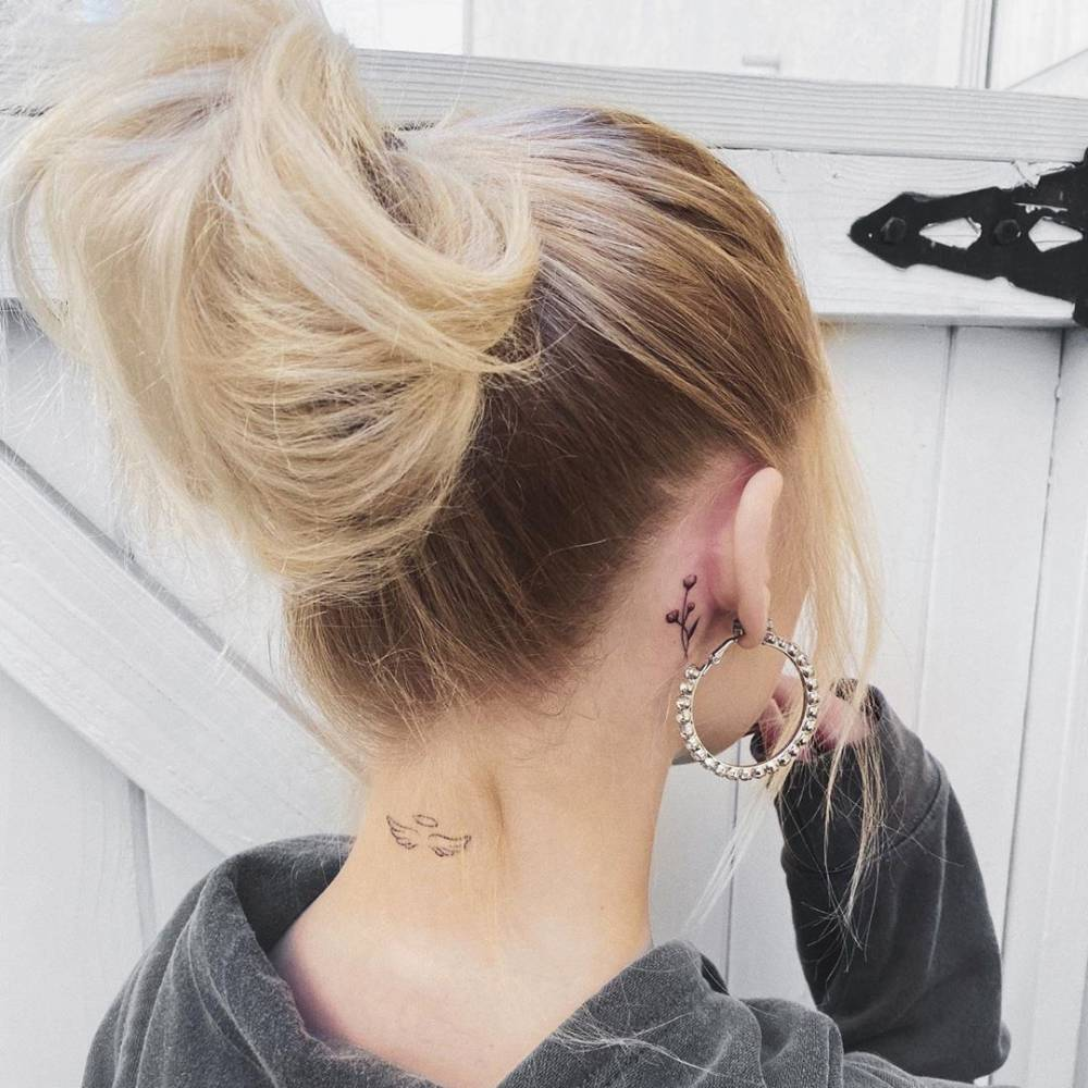Healed angel wings on the back of Loren Gray's neck and a small baby's breath sprout behind her right ear.