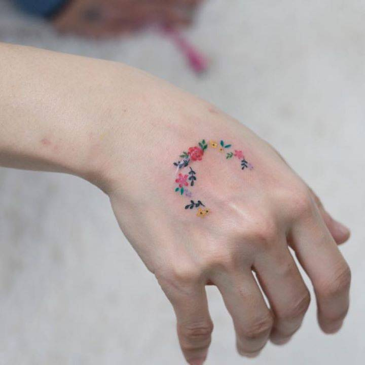 Flower wreath tattoo on the right hand.